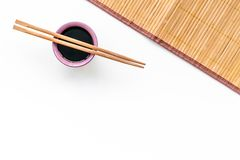 Chinese meal concept. soy sauce in bowl near chopsticks and bamboo table mat on white background top view space for text stock images