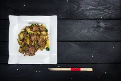 Chinese meat salad with cucumber. Chinese spicy meat salad on white crockery, served with chopsticks. Wooden background with top view Royalty Free Stock Images