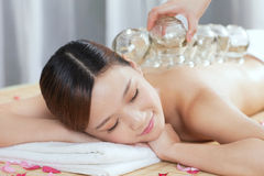A Chinese medicine cupping of the young lady. A young lady receiving  Chinese medicine cupping  at spa salon, indoors Stock Photography