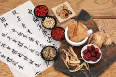 Chinese Medicine. Traditional chinese herbal medicine selection with mandarin calligraphy on rice paper over oak. Translation describes the medicinal functions royalty free stock images