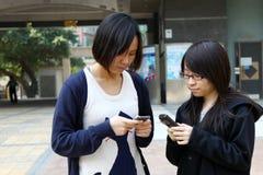 Chinese meisjes die zich op telefoon concentreren Royalty-vrije Stock Foto
