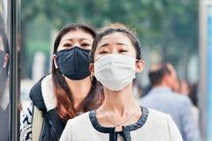 Chinese meisjes met de smog van de adembescherming ageainst, Peking, China Stock Afbeeldingen