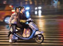 Chinese meisjes op een elektrische fiets bij nacht, Shanghai, China Royalty-vrije Stock Foto's