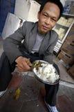 Chinese men eat on street. Chinese men eat rice on street Stock Photography