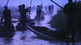 Chinese men rows old boat by using the long stick. Yunnan. China. royalty free stock image