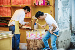 Chinese men with wooden mallets are crushing nuts, Lijiang. LIJIANG, YUNNAN PROVINCE, CHINA - OCTOBER 23, 2015: Chinese men with wooden mallets are crushing nuts Stock Photo