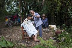 Chinese mens die een kapsel in openlucht op een plattelandsgebied in de rand van thr stad van Yangshuo in China hebben Royalty-vrije Stock Fotografie