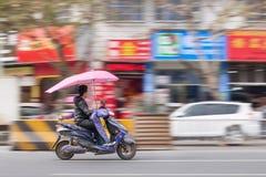 Chinese mens op een elektrische autoped, Yiwu, China Stock Afbeelding