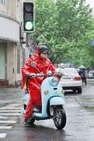 Chinese mens in rode regenkleding op een retro stijlautoped, Shanghai, China Stock Afbeeldingen