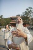 Chinese Mensen die Tai Ji voor de Traditionele Chinese Bouw uitoefenen stock afbeelding