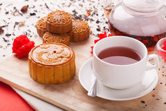 Chinese mid autumn festival foods. Traditional moon cakes on table setting with teacup royalty free stock photography