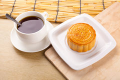 Chinese mid autumn festival foods. Traditional moon cakes on table setting with teacup royalty free stock image