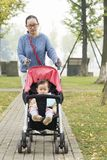 Mom push daughter in baby carseat. Chinese mom push baby carseat and little daughter sitting in outdoor,bun in hand but daughter not hungry stock photography
