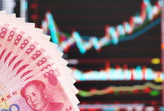 Chinese money. Chinese yuan over stock market Candlestick chart, abstract for Chinese finance or stock market stock photography