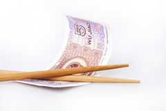 Chinese money. Chinese chopsticks with a a five yuan banknote Stock Image