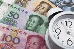 Chinese money (RMB) and clock. Time is money. Business concept. Chinese money (RMB) and clock. 100, 50, 20 and 10 RMB note. Time is money. Business concept Royalty Free Stock Photos
