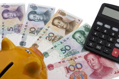 Chinese money (RMB), piggy bank and a calculator. Chinese money (RMB), 100, 50, 20, 10 and 5 RMB note underneath a piggy bank and a calculator. Business concept Royalty Free Stock Photos