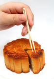 Chinese moon cake. A hand holding a small fork and ready to eat moon cake royalty free stock photography