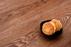 Chinese moon cake -- food for Chinese mid-autumn festival in   a black bowl isolated on wooden background Royalty Free Stock Photography