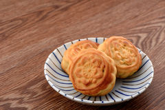 Chinese moon cake -- food for Chinese mid-autumn festival on   a colorful plate isolated on wooden background Stock Photos