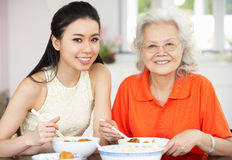 Chinese Mother And Adult Daughter Eating Meal royalty free stock image