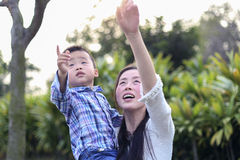 Chinese mother and child raised their hands up and show something. They walk in the park. Green background Royalty Free Stock Image