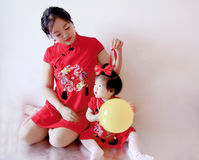Chinese mother and child in red cheongsam have fun. Cute Chinese little baby, 1 year old, wear red cheongsam and with red silk bow on her hair, wear beautiful Stock Photos