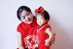Chinese mother and child in red cheongsam have fun. Cute Chinese little baby, 1 year old, wear red cheongsam and with red silk bow on her hair, wear beautiful Stock Photography