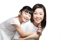 Chinese mother and daughter smiling and playing. Chinese mother piggyback daughter smiling happily. Isolated in white Royalty Free Stock Photo