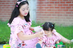 A Chinese mother feed little baby girl on the lawn Stock Photos