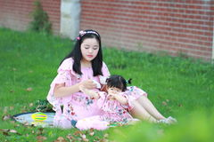 A Chinese mother feed little baby girl on the lawn Royalty Free Stock Photo