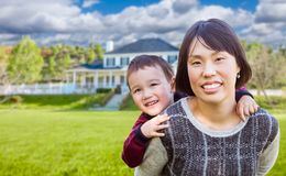 Chinese Mother and Mixed Race Child In The Front Yard of Custom. House Stock Photography