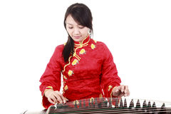 Chinese musician. Chinese zither performer in traditional dress playing zither on white.(close-up Royalty Free Stock Photography