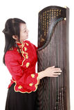Chinese musician. Chinese zither performer in traditional dress with her zither on white Royalty Free Stock Images