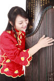 Chinese musician. Chinese zither performer in traditional dress with her zither on white Stock Images
