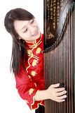 Chinese musician. Chinese zither performer in traditional dress with her zither on white Royalty Free Stock Photos