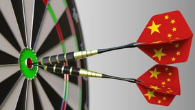 Chinese national achievement. Flags of China on darts hitting bullseye. Conceptual 3D rendering. Chinese national achievement. Flags of China on darts hitting stock photos