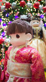 Chinese national custome. A close up view of a doll wearing a traditional Chinese custome with Christmas decorations in the background. Photo taken on November Stock Photo