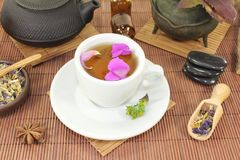 Chinese natural medicine with a cup of tea. And flower petals Stock Image