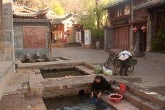 Chinese Naxi-Frau, die auf altem Pool sich wäscht, ist Schimmels-Drache. Stockbild