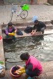 Chinese Naxi-Frau, die auf altem Pool sich wäscht, ist Schimmels-Drache. Stockfotos