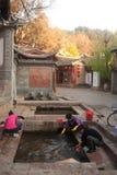 Chinese Naxi-Frau, die auf altem Pool sich wäscht, ist Schimmels-Drache. Lizenzfreies Stockbild