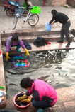 Chinese Naxi-Frau, die auf altem Pool sich wäscht, ist Schimmels-Drache. Stockfoto