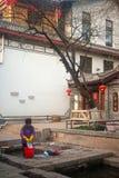 Chinese Naxi-Frau, die auf altem Pool sich wäscht, ist Schimmels-Drache. Lizenzfreie Stockbilder