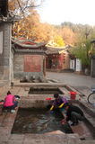 Chinese Naxi woman washing on ancient pool is White horse Dragon. Royalty Free Stock Image