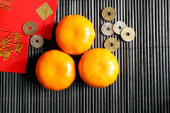 Chinese New Year. Three mandarin oranges, envelopes and coins for Chinese New Year