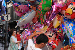 Chinese New Year 2012 - Bangkok , Thailand. BANGKOK - JANUARY 23 : Chinese New Year 2012 - Young girl amazed by balloons in Chinatown, Bangkok, Thailand Royalty Free Stock Photo