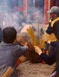 Chinese New Year. Devotees at Wong Tai Sin Temple burn incense for good luck in the coming year royalty free stock images