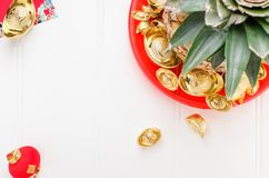 Chinese New year ang pow concept.Top view Pineapple with group o. F gold ingots in red tray on white wood table.on ingots mean wealthy stock photography