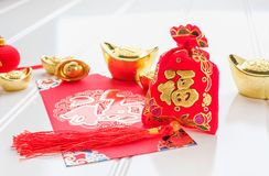 Chinese New year,ang pow red felt fabric bag with gold ingots an. D oranges and flower on white wood table top,Chinese Language mean Happiness and on ingot mean royalty free stock photos